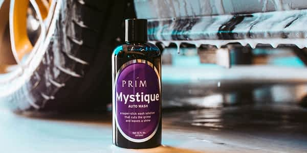 A bottle of Prima Mystique auto wash sits in front of a car dripping with soapy water