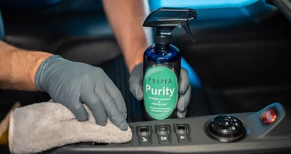 A bottle of Prima Purity interior cleaner and a man polishing a dashboard.